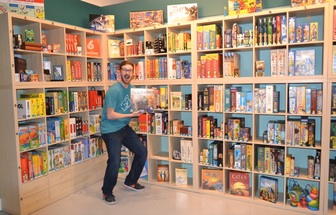 Well Played's Gamemaster shows a favorite board game in front of North Carolina's largest board game library that features 600+ games